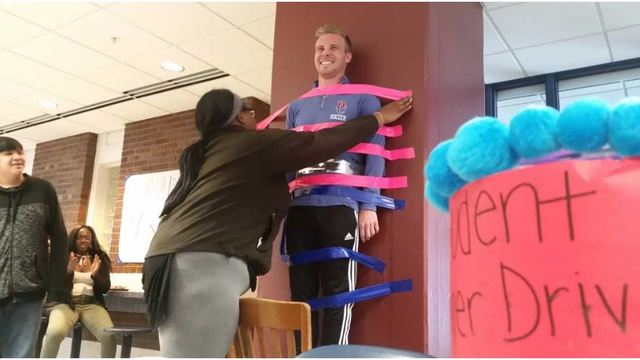 Teacher taped to the wall for a good cause